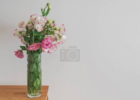 Pink flowers in a glass vase standing near the white wall