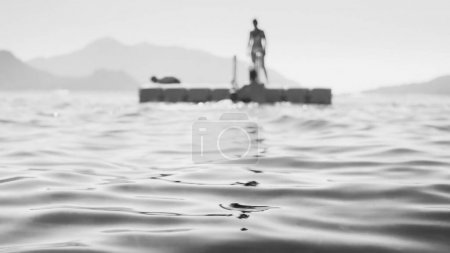 Black and white image of people resting on the floating platform in the sea