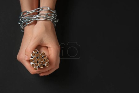女性手与链子和香烟在黑暗的背景。成瘾的概念
