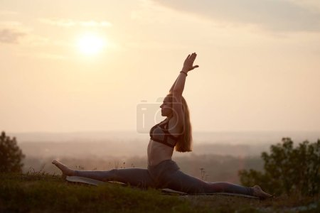 迷人细长长发赤脚年轻女子的剪影在夏天训练装备做体操瑜伽锻炼户外在草山在明亮的粉红色薄雾天空之下在日落或日出.