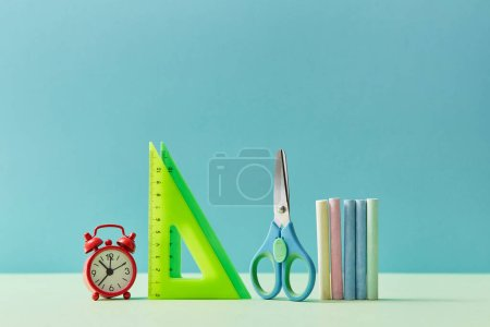 Stationery set. Ruler, scissors, crayons and alarm-clock, copy space. Time to study background. Back to school concept.