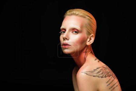 性感裸体纹身的女人摆造型的时尚拍摄, 孤立的黑色