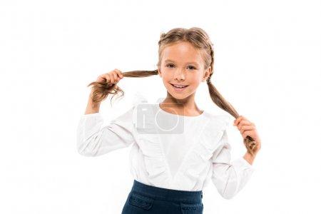 开朗的孩子触摸头发,而看着相机隔离在白色