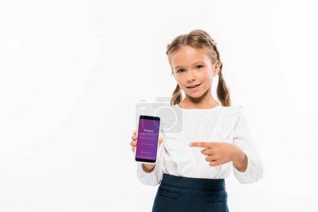 基辅, 乌克兰 - 2019年7月17日:快乐的孩子用手指指着智能手机与Instagram应用程序隔离在白色