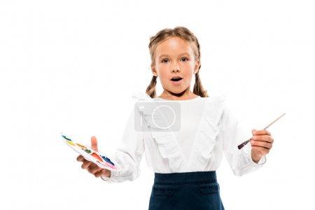 惊讶的孩子拿着五颜六色的水彩调色板孤立在白色