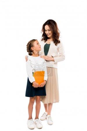 快乐的母亲站在欢快的女儿拿着书孤立在白色