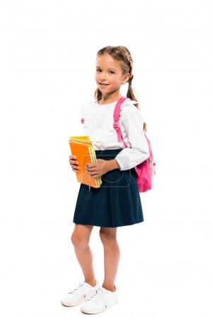 欢快的孩子拿着书,站在粉红色的背包隔离在白色