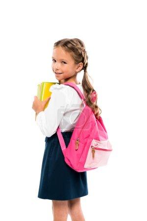 快乐的孩子拿着书,站在粉红色的背包隔离在白色