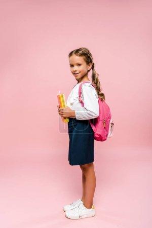 快乐的孩子拿着书,站在粉红色的孤立