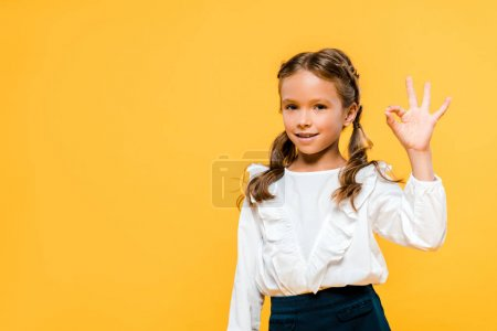 快乐的孩子显示OK标志隔离在橙色