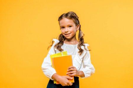快乐的孩子拿着书,微笑着孤立在橙色