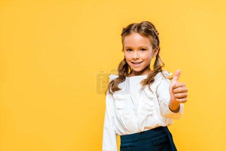 快乐的孩子微笑,并显示大拇指向孤立的橙色