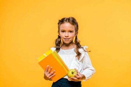 快乐的孩子拿着书和美味的苹果孤立的橙色