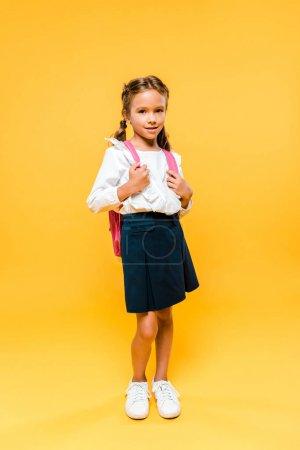 可爱的学童触摸粉红色的背包,而站在橙色