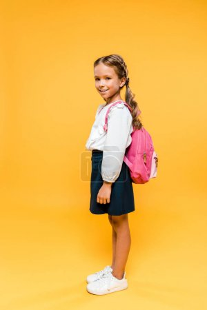 快乐的学童看着相机,而站在橙色