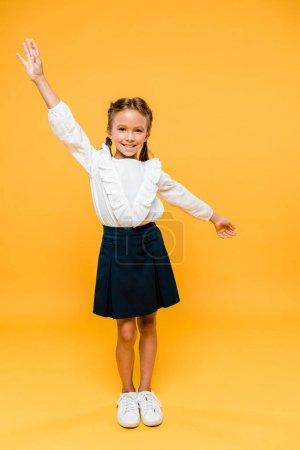 欢快的女学生站在双手以上在橙色