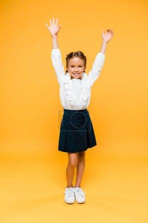 快乐的女学生站在双手以上在橙色