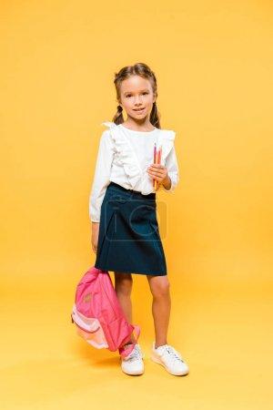 快乐的学童拿着彩色铅笔和粉红色背包在橙色