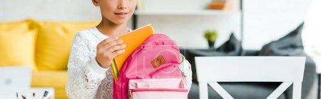 全景拍摄的快乐孩子拿着书附近的粉红色背包在家里