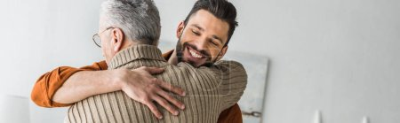 快乐的胡须男子微笑着, 而拥抱父亲在家里的全景照片