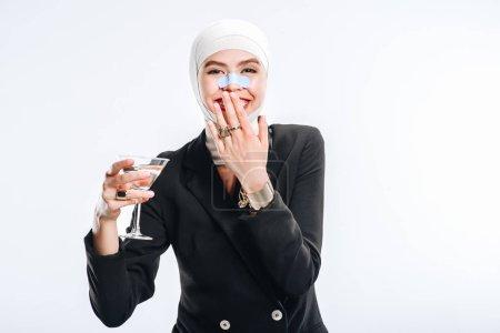 时尚的微笑的妇女与绷带在头在整形手术以后举行了玻璃与鸡尾酒查出在白色