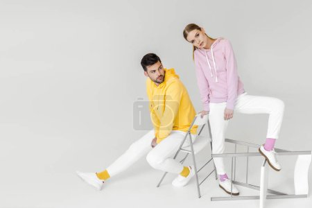 时尚的年轻男性和女性在彩色帽衫坐在白色的椅子上的模型