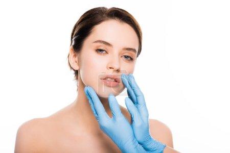 裁剪的意见整形外科医生在乳胶手套触摸在白色孤立的黑发妇女的脸