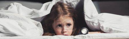 害怕的孩子躲在毯子下,手电筒孤立在黑色