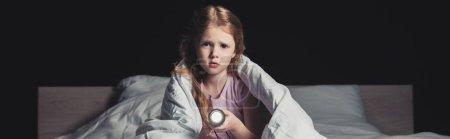 全景拍摄的害怕的孩子坐在床上用品和拿着手电筒孤立在黑色
