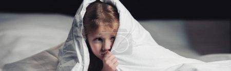 被惊吓的孩子躲在毯子下的黑色全景拍摄