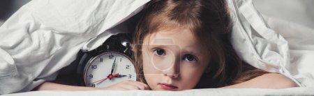 全景拍摄的害怕的孩子躲在毯子下与闹钟
