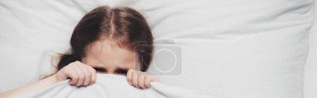 惊恐的孩子躲在毯子下的全景镜头