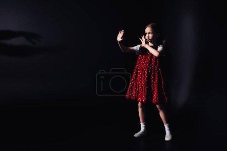 害怕的孩子站在黑暗中,伸出的手在黑色背景