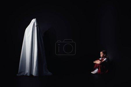 害怕的孩子坐在地板上,看着黑色背景可怕的白色幽灵