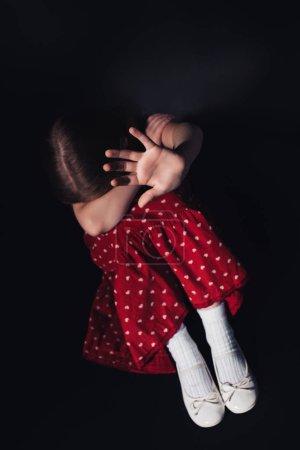 害怕,孤独的孩子坐在黑色背景上伸出的手