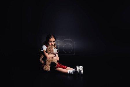 孤独,害怕的孩子坐在地板上,拥抱泰迪熊的黑色背景