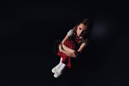 悲伤,害怕的孩子坐在地板上,看着黑色背景的相机