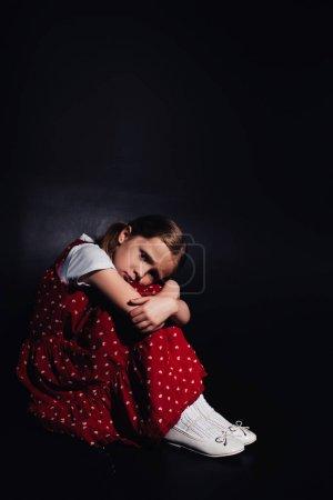 孤独,害怕的孩子坐在地板上,看着黑色背景的相机