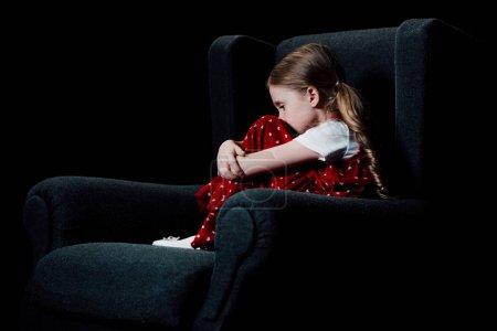 害怕,孤独的孩子坐在扶手椅上孤立在黑色
