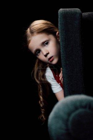 焦虑的孩子看着相机,而躲在扶手椅后面孤立黑色
