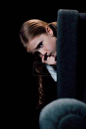 受惊的孩子看着相机,而躲在扶手椅后面孤立黑色