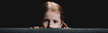 被惊吓的孩子躲在扶手椅后面,看着相机孤立的黑色全景照片