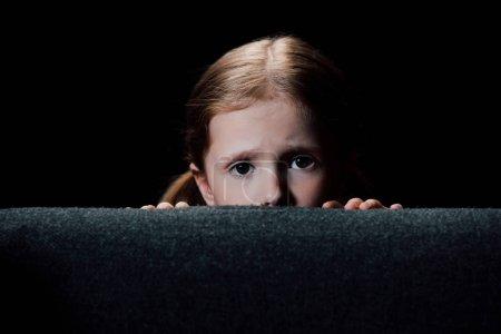 害怕的孩子躲在扶手椅后面,看着相机孤立在黑色