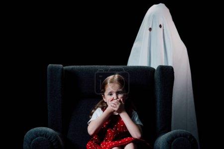 白和害怕的孩子坐在扶手椅上,显示黑色隔离的他标志
