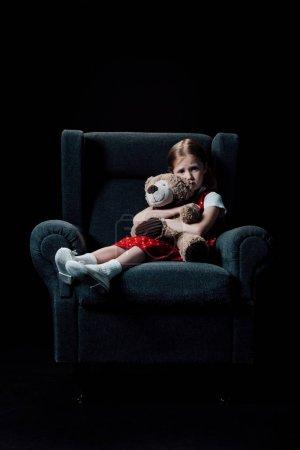 沮丧,害怕的孩子坐在扶手椅上,拥抱泰迪熊孤立在黑色