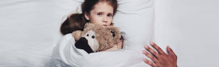 部分视图的男性手附近害怕的孩子躺在床上与泰迪熊,全景拍摄