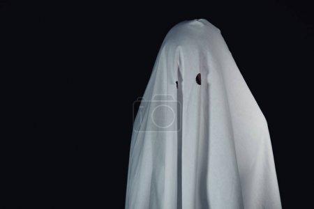 可怕的鬼在白色的床单上孤立在黑色