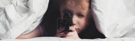 害怕的孩子拿着枪,而躲在毯子下的全景拍摄