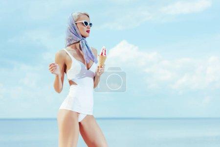 时尚的女孩在时尚的老式泳装举行冰淇淋和摆在附近的海