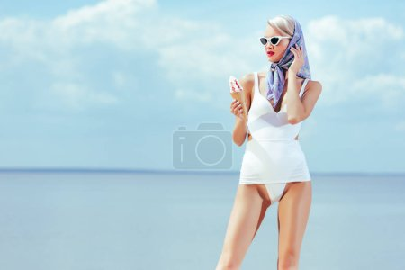 beautiful slim girl in vintage swimsuit holding ice cream and posing near the sea in summer